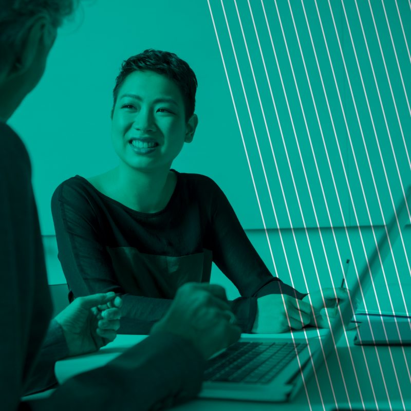 Young Ethnic businesswoman looking at female colleague, smiling. Two women in business meeting with laptop.